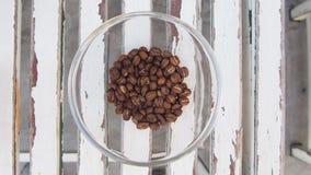 I chicchi di caffè ammucchiano in mucchio di vetro sulla tavola di legno, vista superiore fotografie stock