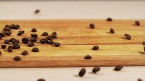 I chicchi di caffè arrostiti arabica cadono movimento lento lungo un primo piano di legno della tavola archivi video