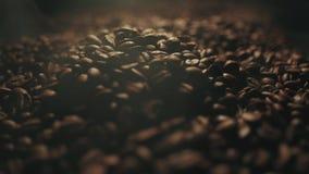 I chicchi di caffè arrostiti fragranti stanno spruzzando sulla tavola di legno Fumo aromatico e fondo marrone al rallentatore stock footage