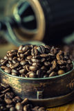 I chicchi di caffè arrostiti si sono rovesciati liberamente su una tavola di legno Chicchi di caffè in un piatto per caffè macina Fotografie Stock Libere da Diritti