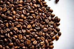 I chicchi di caffè fritti si trovano su una superficie della luce sulla tavola immagine stock libera da diritti