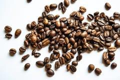 I chicchi di caffè fritti si trovano su una superficie della luce sulla tavola fotografia stock libera da diritti