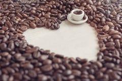 I chicchi di caffè hanno modellato la tazza del giocattolo e del cuore con caffè, concetto Fotografie Stock Libere da Diritti