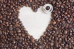 I chicchi di caffè hanno modellato la tazza del giocattolo e del cuore con caffè, concetto Fotografie Stock