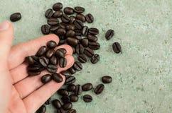 I chicchi di caffè hanno portato dentro una mano Fotografia Stock