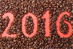 I chicchi di caffè hanno sparso su carta rossa con il numero tirato 2016 Fotografie Stock
