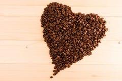 I chicchi di caffè nel cuore modellano su fondo di legno immagine stock libera da diritti