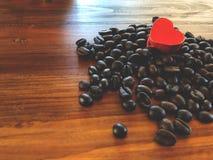 I chicchi di caffè scuri dell'arrosto ed il cuore rosso amano Fotografie Stock Libere da Diritti