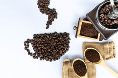 I chicchi di caffè in tazza di caffè hanno modellato con la smerigliatrice di legno fotografie stock libere da diritti
