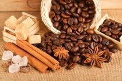 I chicchi e la cannella di caffè su un fondo di tela da imballaggio Fine arrostita del fondo dei chicchi di caffè su Mucchio dei  Immagini Stock