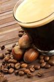 I chicchi e le nocciole di caffè si avvicinano al caffè espresso in uno shor Immagine Stock