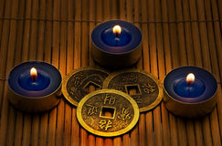 I-ching. Three coins used for i-ching oriental prophecy in candle light Stock Images