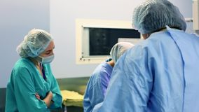 I chirurghi e gli assistenti professionali parlano ed utilizzato il computer durante la chirurgia Funzionano nel funzionamento mo video d archivio