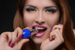I choose the blue one! Portrait of beautiful women holding a nail polish in her teeth stock photo
