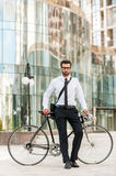 I choose the green way!. Full length of handsome young businessman leaning at his bicycle and looking at camera while standing outdoors Royalty Free Stock Images