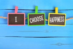 I choose happiness on board. I choose happiness written on color small chalkboard linked rope with clothespin on blue wooden background stock photography