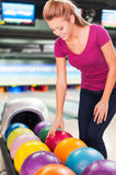 I choose my favorite color. Cheerful young woman choosing bowling ball and smiling while standing against bowling alleys royalty free stock images