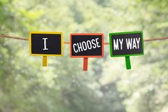 I choose my way on board. I choose my way written on color small chalkboard linked rope with clothespin on nature green bokeh light background stock image
