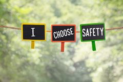 I choose safety on board. I choose safety written on color small chalkboard linked rope with clothespin on nature green bokeh light background stock images