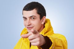 I choose or select you! Good looking young stylish man with dark short hair points with fore finger, chooses something, wears warm. Fashionable yellow anorak Royalty Free Stock Photos