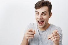 I choose you! Positive emotional male with dark hair looks at camera with joy and points with forefingers at you. I choose you! Positive emotional male with dark Stock Photography