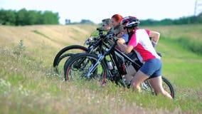 I ciclisti che spingono le bici aumentano una collina archivi video