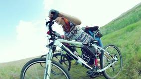 I ciclisti che spingono le bici aumentano una collina stock footage
