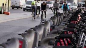 I ciclisti guidano le bici passate di noleggio della città a Londra accanto a traffico video d archivio