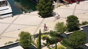 I ciclisti guidano le biciclette dal porticciolo per gli yacht Distretto per Th archivi video