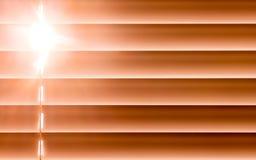 I ciechi orizzontali arancio sulla finestra creano un ritmo con la t fotografia stock libera da diritti