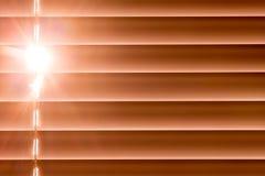 I ciechi orizzontali arancio sulla finestra creano un ritmo con la t immagini stock libere da diritti