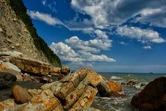 I cieli blu luminosi, rocce taglienti, hanno bagnato ed il bello mare breathtaking fotografie stock