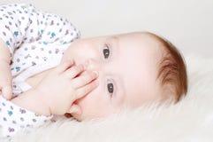 i Cinque-mesi di bambino chiude una bocca con una mano Fotografia Stock