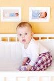i Cinque-mesi di bambino si siede in letto bianco Immagine Stock Libera da Diritti