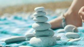 I ciottoli della costruzione della mano del bambino si elevano sulla spiaggia Mucchio delle pietre rotonde equilibrate video d archivio