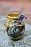 I ciottoli e l'acqua in un barattolo con un fiore si ramificano su fondo vago pietra Fotografia Stock