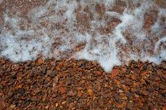 I ciottoli marroni luminosi del mare coperti di lenire ondeggia fotografia stock libera da diritti