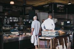I clienti dentro un ` s del macellaio stanno al mercato della città, Londra, Regno Unito fotografie stock libere da diritti