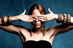 I close my eyes. Woman with hands on the eyes and lot of bracelets, studio shot Stock Photography
