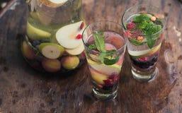 I cocktail dell'estate con frutta stagionale in caraffa di vetro trasparente sta su una tavola in un giardino accanto ad un beche Immagine Stock