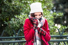 I am cold. Beautiful portrait of a young redhead girl putting her scarf on to protect herself from the harsh winter cold and warm up stock image
