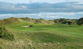 I collegamenti golf il foro con le dune di sabbia nel fondo Fotografie Stock