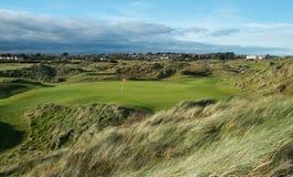 I collegamenti golf il foro di parità 3 nella luce di trascinamento con erba soffiata vento Fotografia Stock