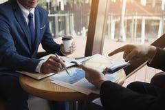 I colleghe di associazione di affari che per mezzo di una compressa per tracciare una carta dei rendiconti finanziari della socie fotografia stock
