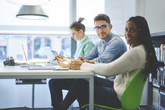 I colleghe sorridenti che hanno riunione informale per discutono le idee Immagine Stock
