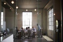 I colleghi di affari ad una riunione in un vetro hanno murato la sala del consiglio fotografie stock libere da diritti