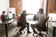I colleghi maschii eccitati danno i pugni urtano in ufficio immagine stock