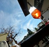 I colori arancio freschi bevono davanti al sole in supporto di macchina fotografica ad angolo immagini stock
