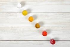 I colori leggeri dei barattoli di gouache sono diagonalmente su fondo bianco nella vista superiore Fotografia Stock