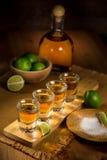 I colpi di tequila raggruppati insieme ad una bottiglia ed alle calce tagliate su un ristorante escludono la tavola Immagini Stock
